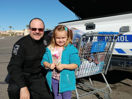 Mike Fulford of the Arizona Highway Patrol went shopping with a kindergartner from Virgin Valley Elementary School during last week's annual holiday event.