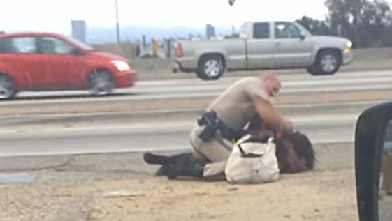 In this July 1, 2014, image from a motorist's cellphone video, a California Highway Patrol officer is seen punching a woman on the shoulder of a Los Angeles freeway.