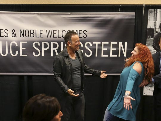 Bruce Springsteen, left, greets a fan wearing a shirt