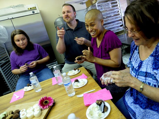 Jowy Barto and LaTonia Barto (center) with their son Gabriel Barto and Joey's mother, Susan Kinsey, have fun participating in a cake tasting at Rolling in the Dough in choose what kind of cake they want for their second wedding.