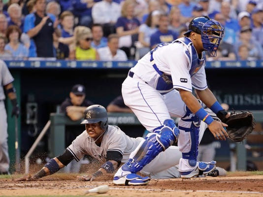 New York Yankees' Starlin Castro beats the tag by Kansas City Royals catcher Salvador Perez to score on a single by Didi Gregorius during the fourth inning of a baseball game Wednesday, May 17, 2017, in Kansas City, Mo. (AP Photo/Charlie Riedel)