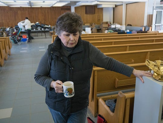 Carol Greening, stands in the clothing bank, located