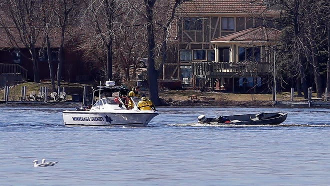 Rescuers approach an unoccupied fishing boat Saturday on Little Lake Butte des Morts. The boat was running in circles.