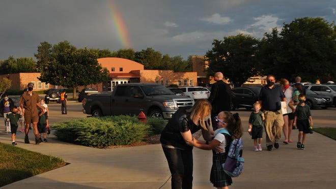 """A rainbow appears as Liz Jacobs, of Salina, gives her daughter, Emersyn Jacobs, 5, advice and a hug before sending Emersyn to her first day of kindergarten near the St. Mary's Grade School Gymnasium on Wednesday morning. """"We excited to get back into a routine. I know that St. Mary's has taken a lot of safety precautions to keep our kids safe,"""" Jacobs said."""