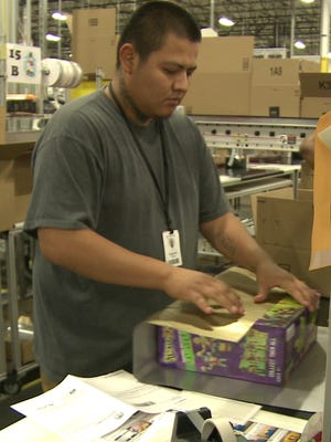 Workers at Amazon's massive fulfillment facility in Phoenix not only pack for shipping, but gift wrap items for Christmas.