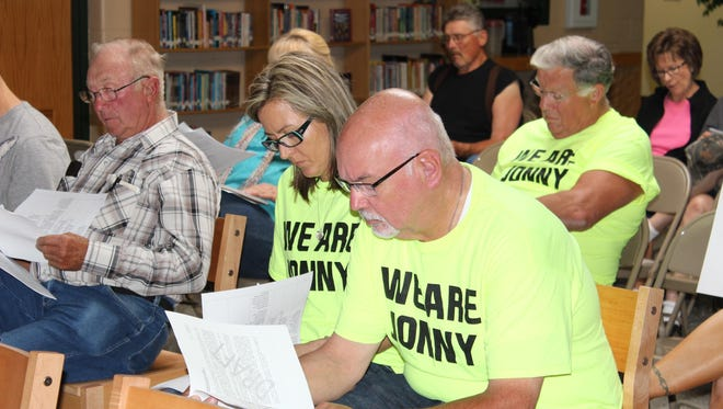 Jonathan Wesener's parents, Angela and Steve, sit at the front of the meeting reading the proposed bullying and anti-harassment policies while the district administrator explains the documents during the Edgar School Board meeting Wednesday, July 15.