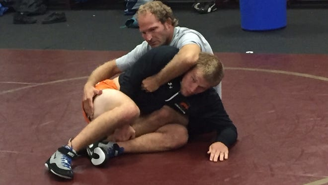Scotti Sentes, center, teachers wrestlers at Riverdale a move as Venice High coach Pat Ryan works on his back.