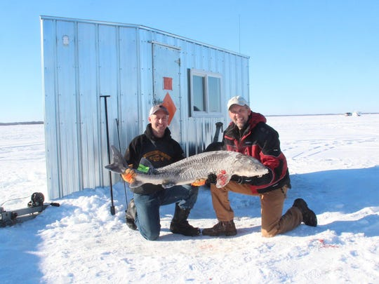 Outdoors Editor Paul Smith (right) and Brent Martin hold the 69-pound sturgeon Smith speared in Martin's shack on Lake Poygan on opening day of the 2016 Winnebago system sturgeon season. The 2019 season is scheduled to start Feb. 9.