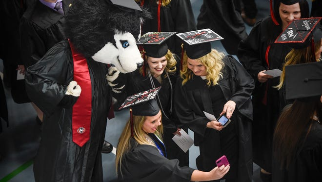 Graduates pose for a photo with school mascot Blizzard before the start of the St. Cloud State University fall commencement ceremony Friday, Dec. 15, at Halenbeck Hall in St. Cloud.