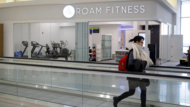In this photo from Jan. 30, 2017, a traveler walks past the soon-to-be-open ROAM Fitness gym at Baltimore-Washington International Airport.