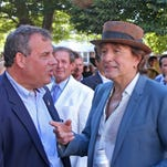 New Jersey Governor Chris Christie, left,  talks with Bon Jovi guitarist Richie Sambora in the paddock at Monmouth Park in Oceanport, NJ on Sunday, Aug. 2, 2015. Both were on hand to see Triple Crown Champion American Pharoah in the $1,750,000 Haskell Stakes at Monmouth Park on Aug. 2, 2015. (Mark Wyville/EQUI-PHOTO via AP)