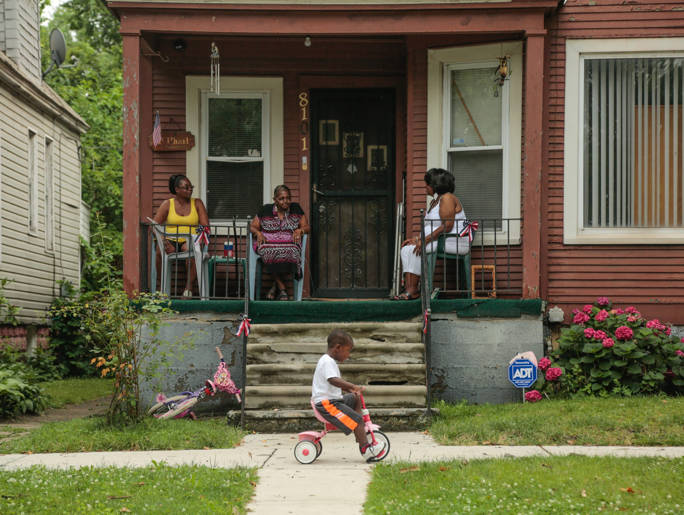 "The McPhail family sits on the front porch of their Vanderbilt Street home in Detroit's Delray neighborhood on July 12, 2017. The family has lived in the home for four decades. ""I've been wanting to go,"" Harriet said. ""But it's my mom. To her this is her home. She purchased this home. It's hers. Why should she leave it? That's how she feel about it. It's home to her."""
