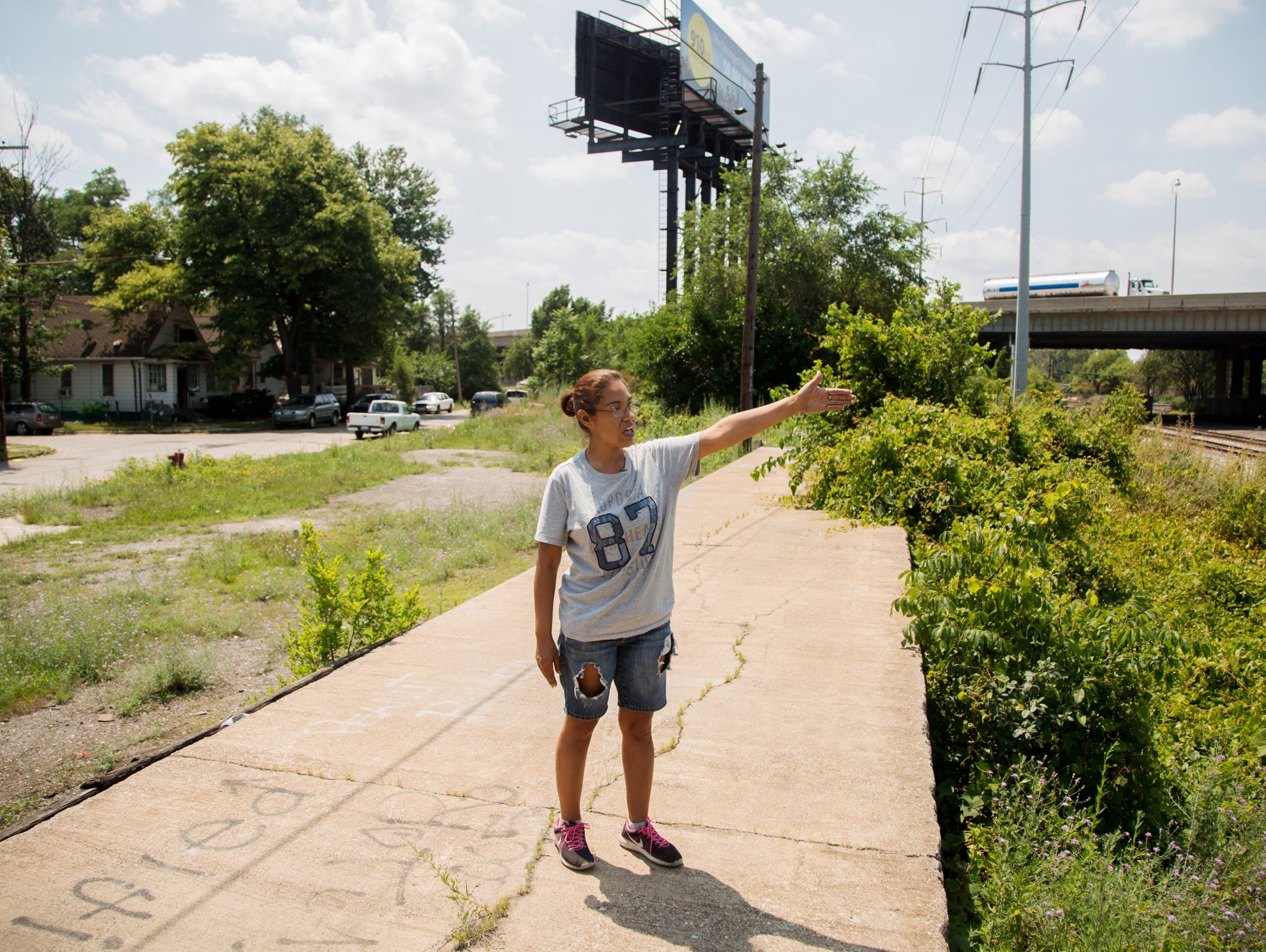 "Lisa Roland, 41, stands on a concrete berm across the street from her Delray home on July 18, 2017. ""We've got the coke piles that they have down at the other end,"" Lisa said. ""We had Wayne Soap and that was the worst smell ever. You knew you were coming to Delray; that smell was horrible. It smelled like rotting flesh 'cause that's what it was. You became accustomed to it, where everybody else was like, 'I'm not going to your house. It smells over there.' We've got the salt mine. We've St. Marys Cement now. We've got Marathon now. We've got the water treatment plant. We've got Zug Island and whatever companies are there. So it's kind of a cluster around here."""