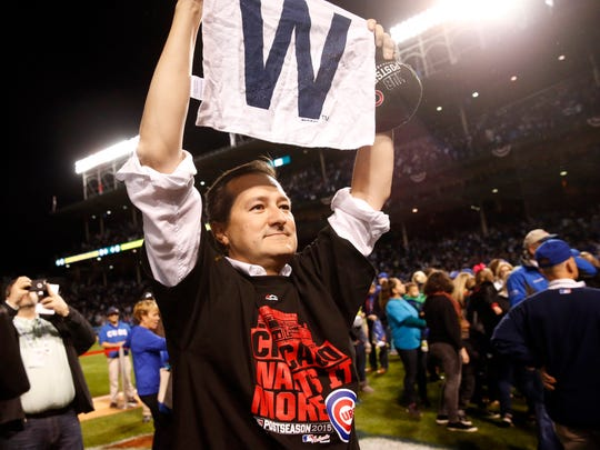 """Cubs owner Tom Ricketts holds up a """"W"""" towel after after winning Game 4 of the NLDS vs. St. Louis."""