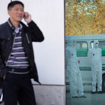 A North Korean man speaks on his mobile phone as medical personnel dressed in protective suits wait by an ambulance, at the Sunan International Airport, in Pyongyang, North Korea, on Oct. 27, 2014.