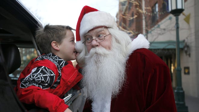 AJ Farner, 5 of Bloomfield Hills whispers his Christmas list to Mike Short, a Santa helper, from Westland, while downtown in Birmingham on Dec. 14, 2012.
