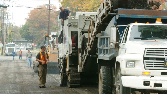 Henderson city workers mill the surface off of Ingram St. between Second and First Streets in this October, 2004 file photo.