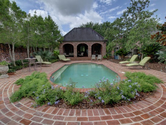 The large pool is surrounded by a brick deck and landscaping.
