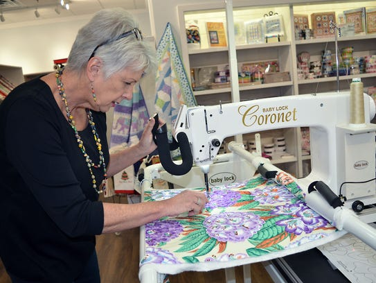 Cotton Blossom Fabric Shop co-owner Cathy Dixon demonstrates