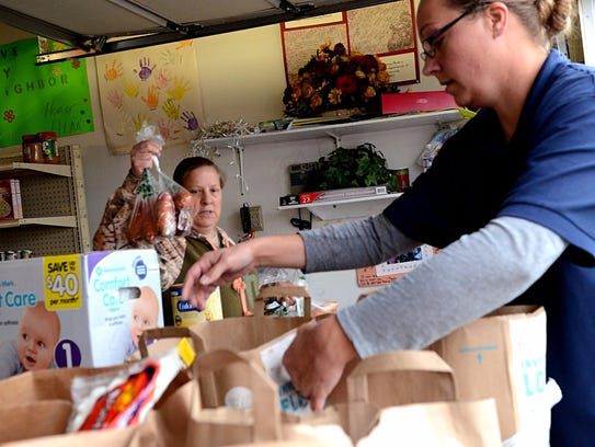Volunteers help gather food donations in bags to distribute