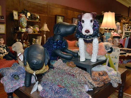 Handmade pet sweaters in various sizes and colors are