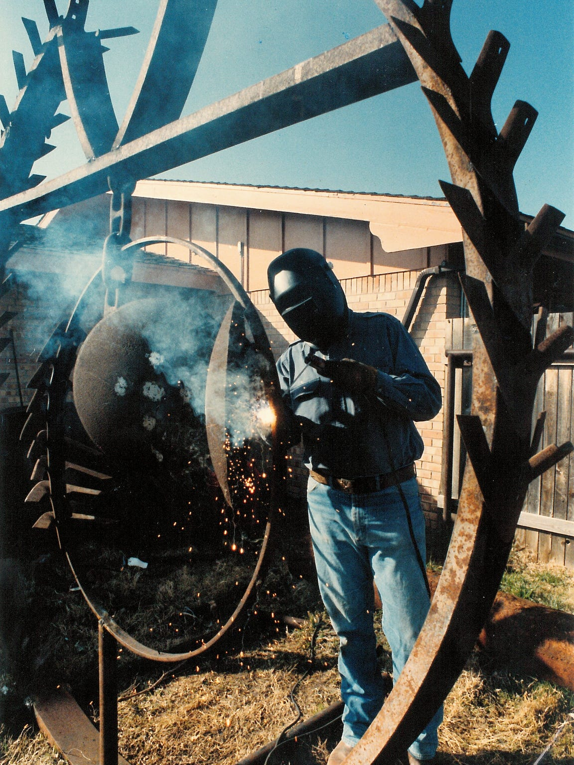 "Tom Niblo works on his sculpture, ""Industrial Dichotomy,"" in his back yard in a 1993 photo. The sculpture is made of scrap iron from farm and oilfield equipment."