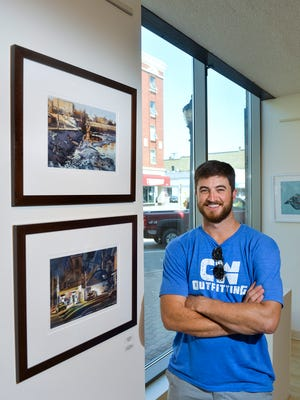 Local artist Dan Mondloch stands Thursday, Sept. 1, with two of his paintings at Gallery St. Germain. He is one of the exhibitors at the SCSU Alumni Art Exhibition at the gallery in downtown St. Cloud.