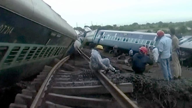 In this image made from video, people gather by the twisted track alongside two derailed trains in Harda in Madhya Pradesh state, India, Wednesday, Aug. 5, 2015.
