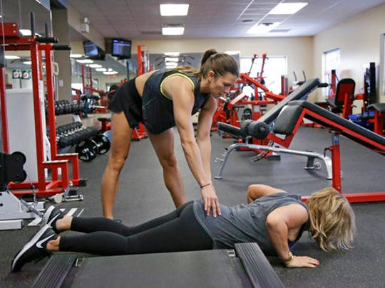 In this Saturday, Feb. 18, 2017, photo, Associated Press writer Jenna Fryer, bottom, gets some workout instruction from Danica Patrick at Daytona International Speedway, in Daytona Beach, Fla. Patrick is really serious about health and clean eating, and as her driving days may be nearing an expiration date, a second career in lifestyle and fitness could be up next.