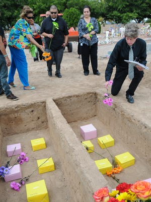 Attendants gather at St. Joseph's Cemetery on Wednesday for the annual Pauper Funeral. Flowers were placed over the ashes of 14 people whose bodies were not claimed by friends or family. Each of the bodies has been cremated, and the remains and personal effects have been in the custody of the Dona Ana County Health and Human Services Department for two years, as required by state law. The names of those who were buried: Jack Donald Jones, 84; Elaine M. Barnella, 83; Guillermo G. Guevara, 71; Madison Miller, 71; John Flores, 64; Christine K. Yeager, 64; Rodger Mason, 62; Steven Patterson, 60; Stephen Lieb, 56; Cheryl Maggiore, 55; Marilyn Davis, 55; Paula Wagner, 53; Robert W. Woodruff, 46; and Patrick James Sanders, 43.