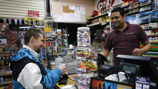 Carl Harper, 45, of Delhi, purchases a Powerball lottery ticket from Sudhakar Gundaji at Garfield Mini-Mart in downtown Cincinnati on Wednesday, Jan. 6, 2016. Wednesday's Powerball jackpot is an estimated $700 million.