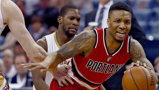 Portland Trail Blazers guard Damian Lillard (0) dribbles past New Orleans Pelicans guard Toney Douglas, rear, and center Omer Asik, left, during the first half of an NBA basketball game in New Orleans, Friday, March 18, 2016. (AP Photo/Max Becherer)