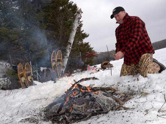 Tim Watson of Waunakee cooks two hot dogs during a lunch break on Lake Three in Ashland County.