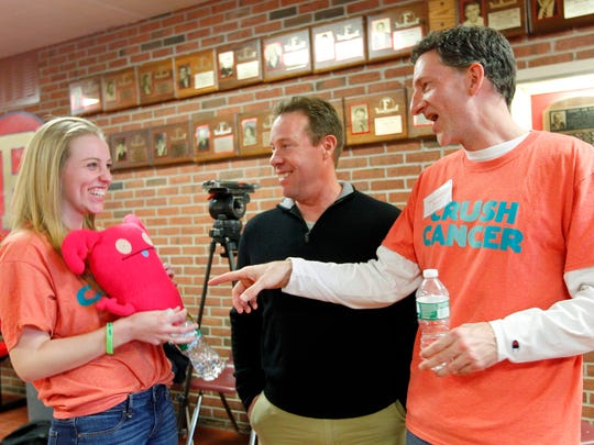 Mike Metzler, far right, shares a laugh with   Erin Nannen, left,  and Erin's father, Jay, all of Fairport, during the Crush Cancer Concert at Fairport High School on Saturday. The concert honored Metzler's daughter, Hannah, who recently died of cancer.