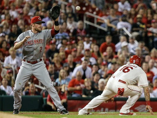 St. Louis Cardinals Kolten Wong, right, is caught in a rundown by Cincinnati Reds shortstop Zack Cozart during the seventh inning of a baseball game Saturday, Sept. 20, 2014, in St. Louis. (AP Photo/Sarah Conard)