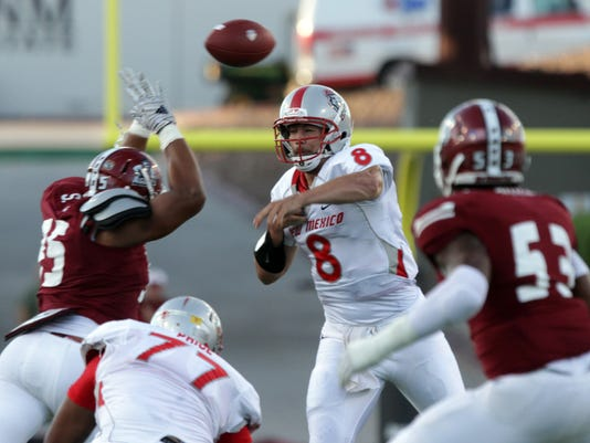 New Mexico quarterback Cole Gautsche fires a pass between New Mexico State rushers during the first quarter of an NCAA college football game Saturday Sept. 20, 2014 in Las Cruces, N.M. (AP Photo/Victor Calzada)