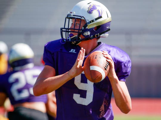 Kirtland Central quarterback Bryson Dowdy searches for an open receiver during football practice on Wednesday, Aug. 17, 2017 at Bronco Stadium in Kirtland.