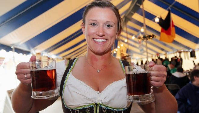 Katrina Patterson of Milwaukee holds a pair of steins of beer during Oktoberfest at Al and Al's Steinhaus Saturday October 3, 2015 in Sheboygan.