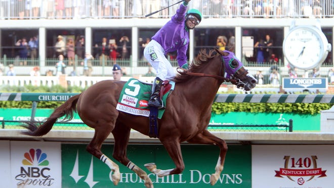 Victor Espinoza aboard California Chrome (5) celebrates as they cross the finish line to win the 2014 Kentucky Derby at Churchill Downs.