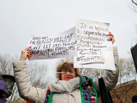 Rev. Sharon Stanley-Rea holds up hand-made signs as