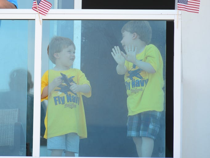 Two young boys enjoy the air show from their hotel