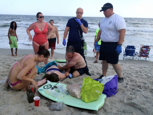 People assist a teenage girl at the scene of a shark attack in Oak ...
