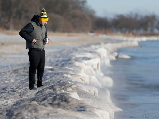 A man takes a look at the shoreline before Milwaukee's