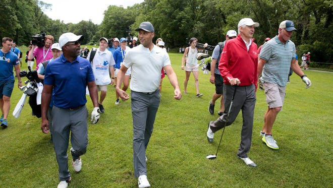 Darius Rucker (from left), Derek Jeter, Andy North and Brett Favre walk down the 11th fairway at University Ridge on Saturday. The foursome took part in a celebrity event right behind the final group at the American Family Insurance Championship on Saturday in Madison.