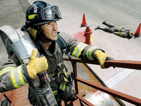 """Las Cruces firefighter Steve Alexander demonstrates a portion of the department's physical ability test on Thursday at Fire Station 4 on Missouri Avenue. In the background is a mannequin that is used during the """"Dummy Drag"""" portion of the test. Firefighters and fire personnel saw the highest pay increase — about 4 percent — of any group employed by the city of Las Cruces."""