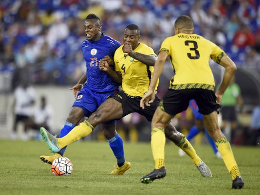 Haiti forward Jean-Eudes Maurice (21) battles for the ball against Jamaica defender Wes Morgan (4) and Michael Hector (3) during the second half of a CONCACAF Gold Cup soccer quarterfinal match on Saturday in Baltimore. Jamaica won, 1-0.