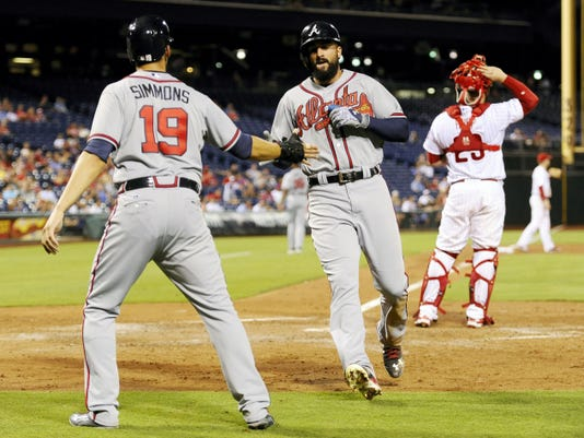 Atlanta's Andrelton Simmons (19) and Nick Markakis celebrate at home plate after scoring on Hector Olivera's RBI double in the fourth inning of Monday's game against Philadelphia.