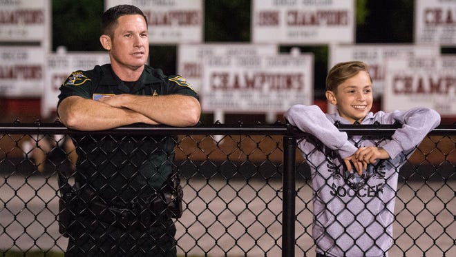 Martin County Sheriff's Office School Resource Deputy Dale Hardy, who is assigned to South Fork High School, and Connor Critoph, 12, of Indiantown, watch South Fork take on Olympic Heights during the high school girls soccer regional quarterfinal game Tuesday, Feb. 6, 2018, at South Fork High School in Tropical Farms.