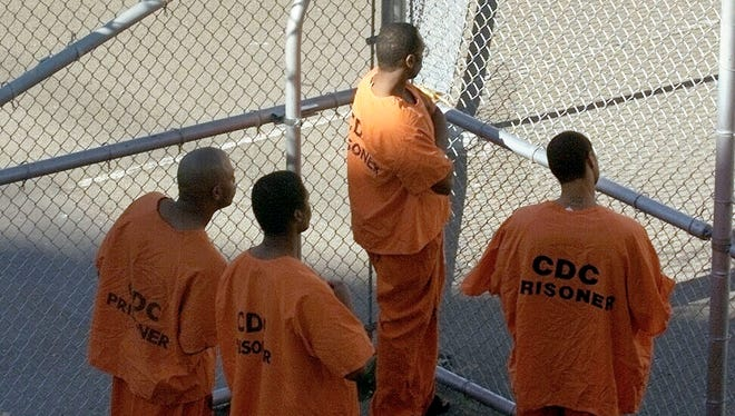 This 2001 file photo shows prisoners in orange jumpsuits waiting as they're being processed at San Quentin State Prison in Marin County north of San Francisco. A new study suggests that having a parent incarcerated can be as tough on a child as a parent's divorce or death.