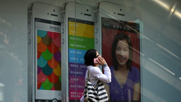 A woman uses a mobile phone as she walks past an Apple iPhone 5 poster on Sept. 11 in Beijing.  Apple's lower-cost iPhone 5C will retail for more than $700 in China, putting it out of reach of most consumers and raising questions over the firm's ability to build sales in the world's biggest mobile market.